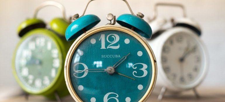 Three alarm clocks on a surface.
