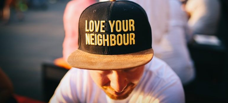 A man wearing a love your neighbor hat.