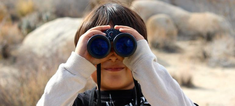 a kid with binoculars as a way to keep your kids entertained during a long distance move