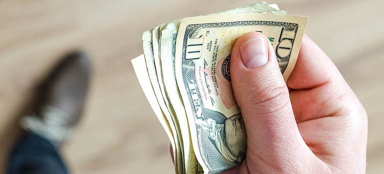 a hand holding money bills