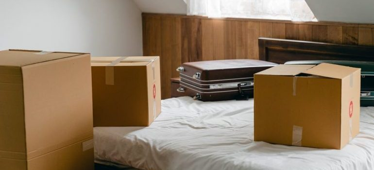 cardboard boxes and a case on a bed