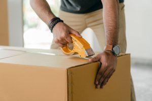 Man taping a cardboard box