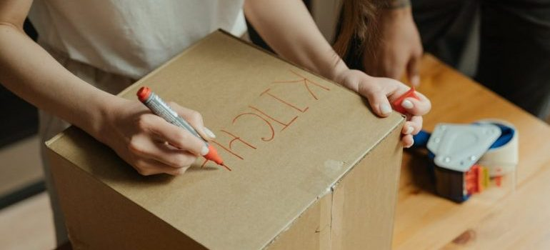 woman writing on a box