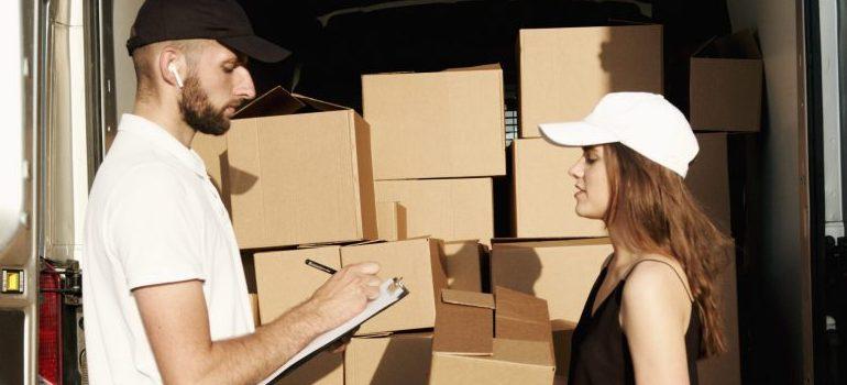man writing down, woman holding a moving box