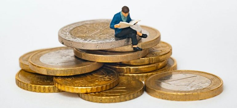 Figurine seating on coins