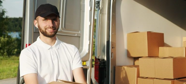 man carrying a box while standing by a truck full of boxes