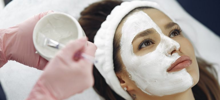 a woman lying at the spa center while someone is putting a mask on her face
