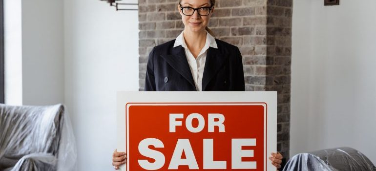 A realtor with a For Sale sign