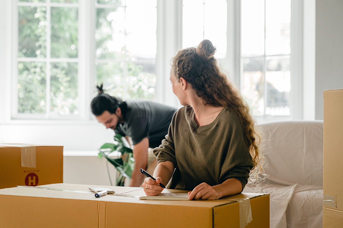 move long-distance on a budget. young couple is packing up and boxing up their personal belongings in preparation for a move.